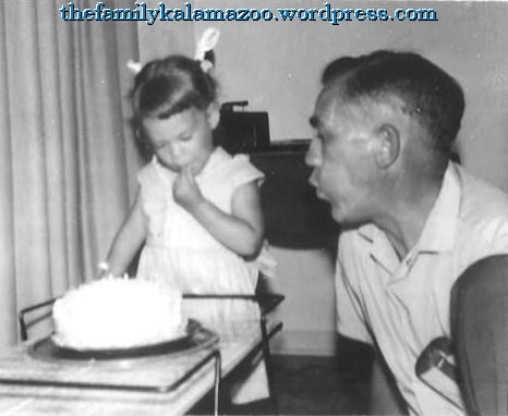 Grandpa helping 2-year-old me blow out the candles on my birthday cake